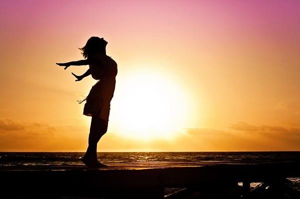 אישה פורסת את ידיה באושר